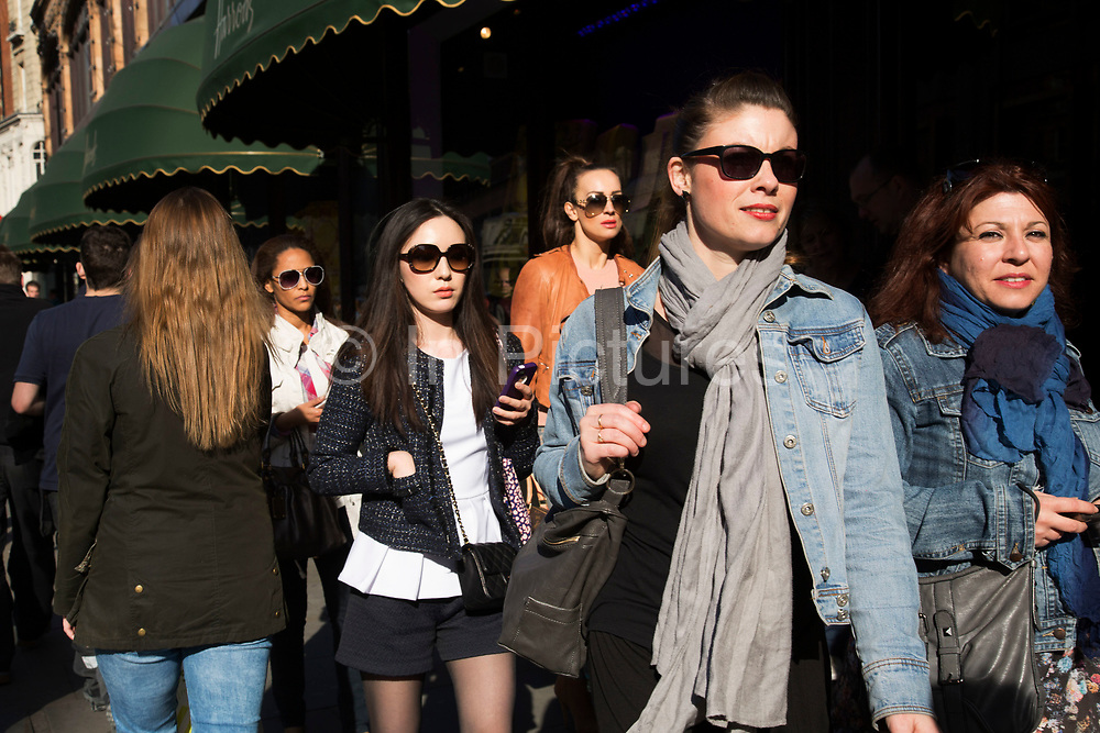 Shoppers outside Harrods department store in the exclusive area of Knightsbridge. In a selected few boroughs of West London, wealth has changed over the last couple of decades. Traditionally wealthy parts of town, have developed into new affluent playgrounds of the super rich. With influxes of foreign money in particular from the Middle-East. The UK capital is home to more multimillionaires than any other city in the world according to recent figures. Boasting a staggering 4,224 'ultra-high net worth' residents - people with a net worth of more than $30million, or £19.2million.. London, England, UK.