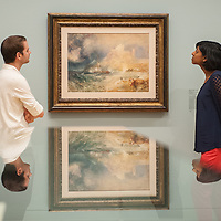 London, UK - 8 September 2014: two gallery assistants pose next to 'Bamborough Castle c.1837' by J.M.W. Turner