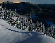 moonlight on the snowcovered forest and Morge Lakes and the Puyallup Ridge with the warm glow from Puget Sound on the horizon in the Washington state Cascade Range west of Mount Rainier