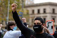 A man wearing a facemask making a Fight The Power gesture  during a Black Lives Mater rally on 06 June, 2020 in Melbourne, Australia. This event was organised to rally against aboriginal deaths in custody in Australia as well as in unity with protests across the United States following the killing of an unarmed black man George Floyd at the hands of a police officer in Minneapolis, Minnesota. (Photo by Dave Hewison/ Speed Media)