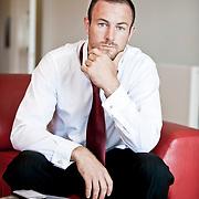 caucasian man in suit sat on sofa