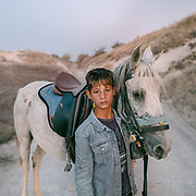 "A boy enjoys a horse ride in Cappadocia, meaning ""the land of the beautiful horse""."