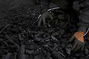 A coal merchant sorts through pieces of coal to sell to customers in Kabul, Afghanistan, February 2, 2020. The capital Kabul, a city of some 6 million, ranks as one of the most polluted cities in the world – contesting amongst other polluted capitals such as India's New Delhi or China's Beijing. Many cannot afford electricity and so burn coal, garbage, plastic and rubber in their homes to keep warm during the cold winter months. Old vehicles and generators that run on poor quality fuel release vast amounts of toxins into the city's air.