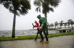 October 7, 2016 - Tallahassee, FL, USA - A couple walk along the Sanford Riverwalk along Lake Monroe as strong winds and rain continue from Hurricane Matthew in downtown Sanford on Friday, October 7, 2016. (Credit Image: © Jacob Langston/TNS via ZUMA Wire)