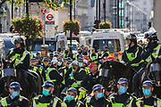 """Police form lines during a """"Resist and Act for Freedom"""" protest against a mandatory coronavirus vaccine, wearing masks, social distancing and a second lockdown, nearby Canada House in Trafalgar Square, London on Saturday, Sept. 19, 2020. The event, which began at noon, drew a broad coalition including coronavirus sceptics, 5G conspiracy theorists and so-called """"anti-vaxxers"""". Speakers at the event accused the government of attempting to curtail civil liberties. (VXP Photo/ Vudi Xhymshiti)"""