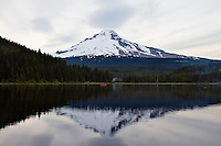 A red boat on peaceful Trillium Lake in the reflection of Mt Hood