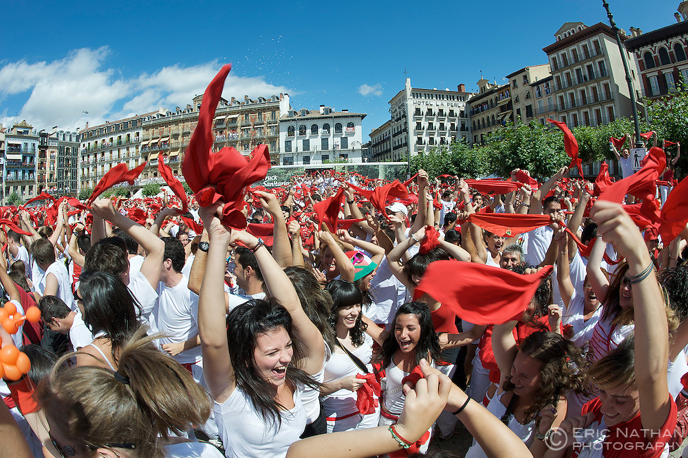 Crowds in traditional red and white costumes during the opening ceremony of the annual festival of San Fermin (aka the running of the bulls) in Pamplona, Spain.