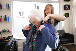 Hairdresser helping old lady with her coat.