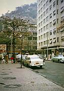 Streets, shops, cars parked in Copacabana, Rio de Janeiro, Brazil 1962 shanty town favela housing on hillside