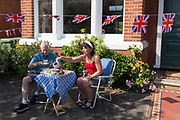 As the Coronavirus lockdown continues over the May Bank Holiday, the nation commemorates the 75th anniversary of VE Day (Victory in Europe Day, the day that Germany officially surrendered in 1945) and in Dulwich, neighbours and residents emerge from their homes to party while still observing social distancing rules. A couple enjoy tea and cake beneath Union Jack bunting outside their home, on 8th May 2020, in London, England.