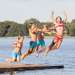 four children jumping into a lake