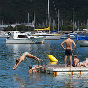 A teenage girl dives into the water from a pontoon at Waikawa Bay near Picton.  Waikawa is the home of New Zealand's 3rd largest Marina only minutes away from  Queen Charlotte Sounds near Picton at the top of the South Island of New Zealand,  28th January 2011. Photo Tim Clayton