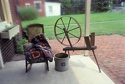 antiques spinning wheel, quilt, rocker, butter crock.