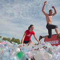 Competitor jumps to run through plastic bottles during the Brutal Run extreme obstacle course race in Budapest, Hungary on August 30, 2014. ATTILA VOLGYI