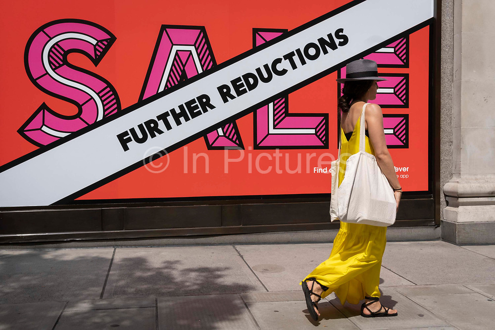 A shopper walks past Selfridges whose Summer Sale is advertised in their window banners on Oxford Street in the West End on Covid Freedom Day. This date is what Prime Minister Boris Johnsons UK government has set as the end of strict Covid pandemic social distancing conditions with the end of mandatory face coverings in shops and public transport, on 19th July 2021, in London, England.