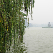 Turtle Tower (Thap Rua), on a small island in the middle of Hoan Kiem Lake in the heart of Hanoi is partially obscured by a thick morning fog. In the foreground, at left, are some of the low-hanging trees on the lake's shore.