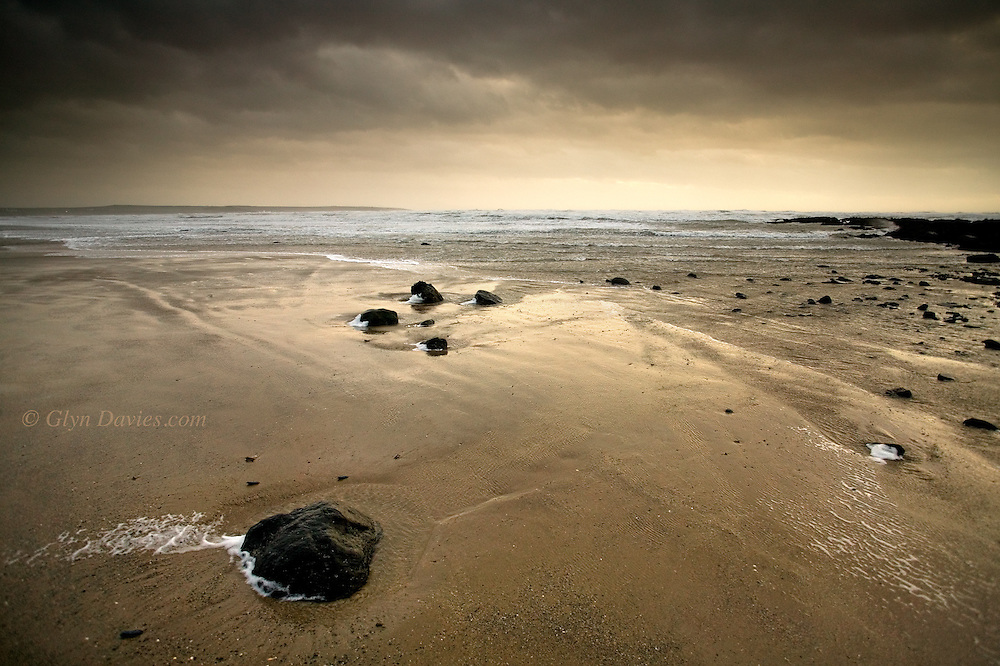 Windswept Broad Beach at Rhosneigr, West Anglesey, Wales, in a gale and rainy weather at sunset..