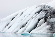 Rock debris is visible on the face of a large iceberg that is floating in the glacial lagoon of Jökulsárlón in southern Iceland. The glacial lake is full of icebergs that have fallen from the Breiðamerkurjökull glacier.