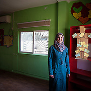 """Nisreen, 30, her husband and four kids, ages 6-11, fled to Jordan two years ago after her husband was injured in the war; they came to Jordan where his siblings, who could help take care of him, were already living (He is now completely healed). Nisreen is a volunteer arts and crafts instructor in the Nubader No Lost Generation Project at Mercy Corps' partner organization AJDT. The No Lost Generation Project aims to provide at risk Syrian and Jordanian youth with alternative education, skills, and psychosocial services to address profound stress the children have gone through. One of the most important things Nisreen brought with her from Syria is her smile and her positive attitude.<br /> <br /> Malik Betar, Mercy Corps field officer: """"If you ask anyone here in the CBO about Nisreen, the first thing they will talk about is her smile and how her smile and positive energy gives you support. <br /> <br /> """"When I left Syria I thought that I would never smile again or have this positive attitude again because all of the rest of my family went to Lebanon. But when I met the Jordanians, especially my neighbors, and when I came to the center (AJDT) and I met all of the other volunteers and instructors, I felt as if I were at home and everyone was my family, and then I found my smile and spirit."""" Mafraq, Jordan, May 2015."""