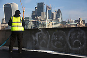 Ativists from the air pollution campaign group Stop Killing Londoners spray paint their message on City Hall and the walls by the Thames on 21st March 2018 in London, United Kingdom. Many thousands of Londoners and people in major UK cities die every year from pair pollution from mainly diesel emmissions. The activists want the Mayor of London, to do much more to curb the air pollution in London. The spray paint is chalk based and easily removed. In spite of this the activists were arrested for criminal damage. The action is part of a long running campaign and all 4 activists broke their bail conditions imposed the day before from a previous similar action.