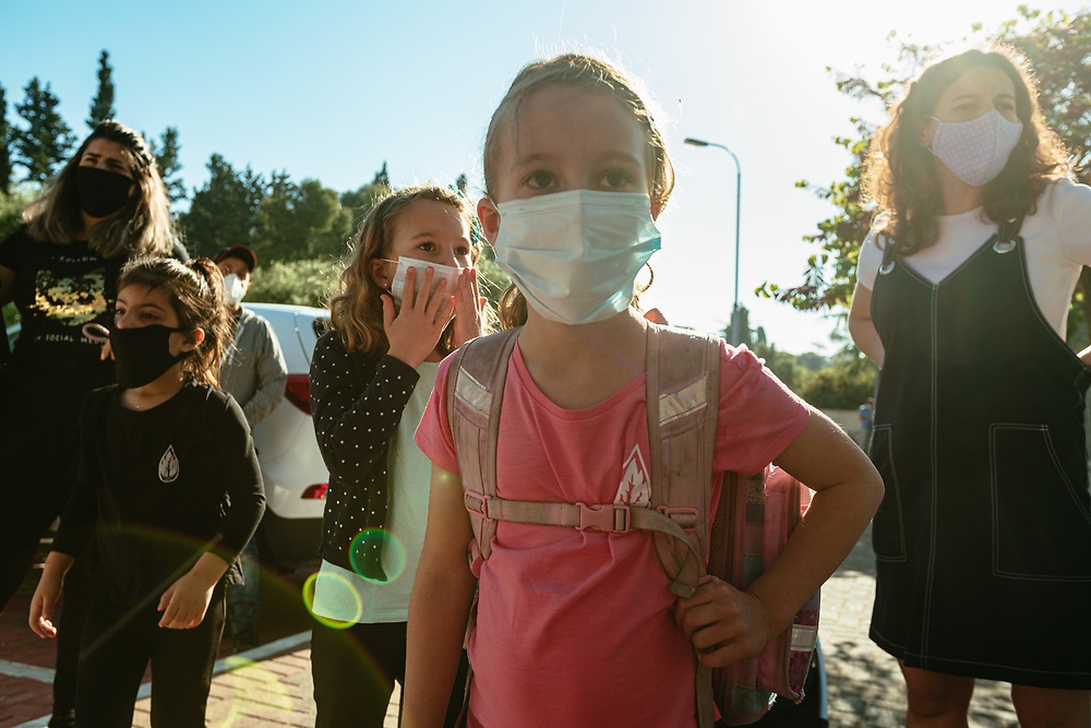 Twin girls Alma (3rd R) and Clil (2nd R), and their mother Anna Michel (R), wearing protective face masks, are seen as they await their turn to enter the elementary school where the girls study, in Jerusalem
