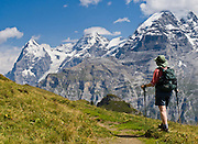"From Wasenegg Ridge, a hiker sees peaks of Eiger (the Ogre, 13,026 feet), Mönch (the Monk), and Jungfrau (the Virgin, 13,600 feet), in the Berner Oberland, Switzerland, the Alps, Europe. The Bernese Highlands are the upper part of Bern Canton. UNESCO lists ""Swiss Alps Jungfrau-Aletsch"" as a World Heritage Area (2001, 2007)."
