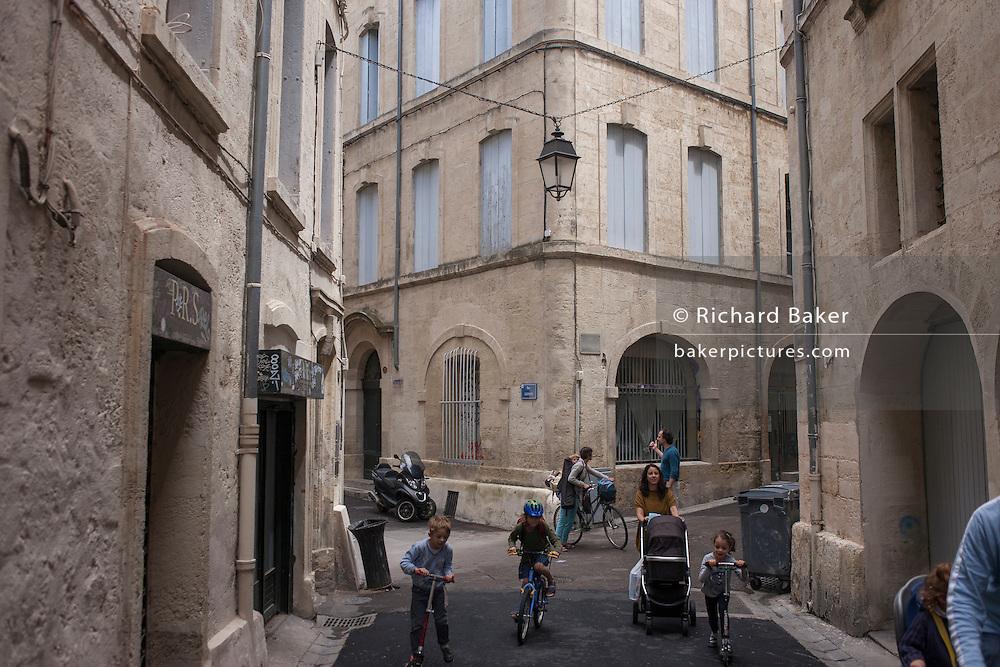 Children and adults under street lantern in narrow Montpellier stret, France.