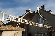 Metal sign shining in sunlight Saint Aldhems catholic church, Malmesbury, Wiltshire, England, UK