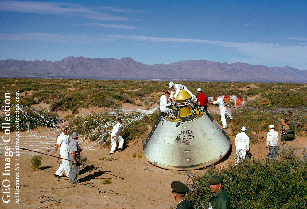 Minutes after Apollo's landing, technicians clamber over the capsule amid the sand and sagebrush of the impact area.