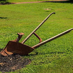 Morrisville, PA, USA - June 23, 2012: A rusty, old hand plow at the edge of a plot.