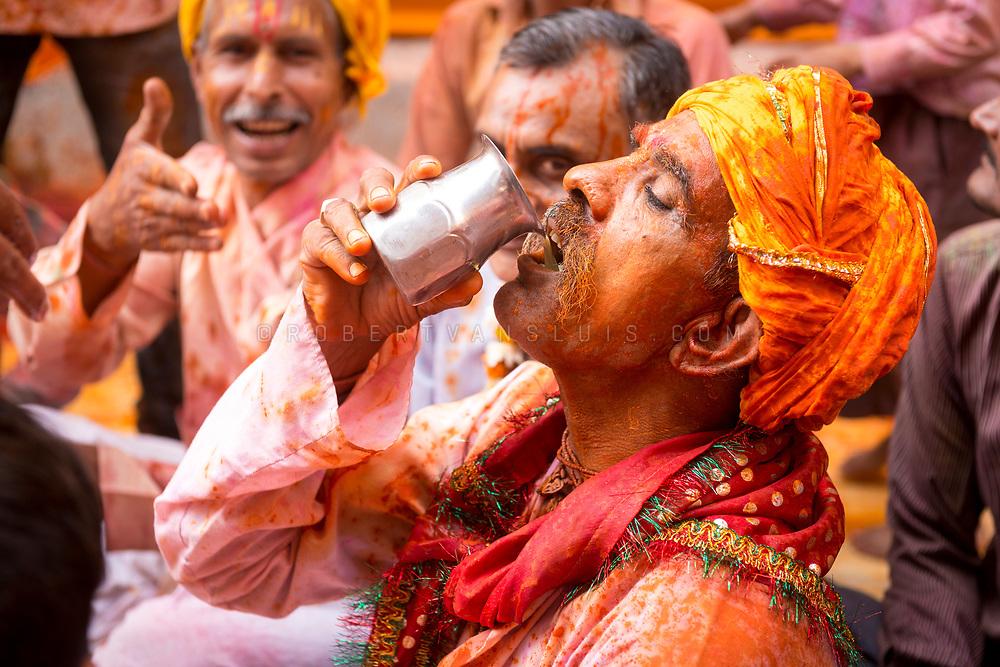 Men drinking bhang lassi (yoghurt drink mixed with marihuana) during religious chanting at the Huranga festival, Dauji temple, Baldeo, India. Photo © robertvansluis.com