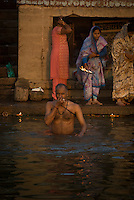 A pilgrim taking a holy bath in the River Ganges during the festival of Kartik Poornima in Varanasi, Uttar Pradesh, India