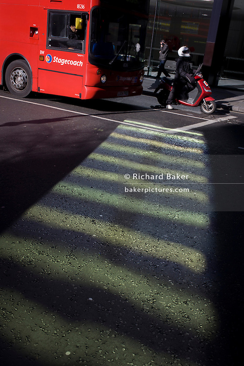 A red London bus and red scooter stop at lights by reflected green light shining from a corporate building in the City of London.