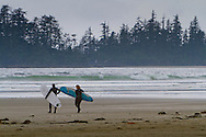 Surfers in full wet suits brave the cold water at a surf break in Tofino on Vancouver Island, British Columbia