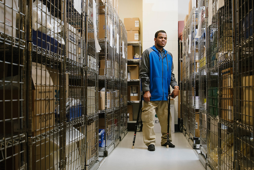 A member of the first class of Goodwill's Project SEARCH class photographed in the supply room for Spaulding Rehabilitation Hospital for the Mass Housing Annual Report.