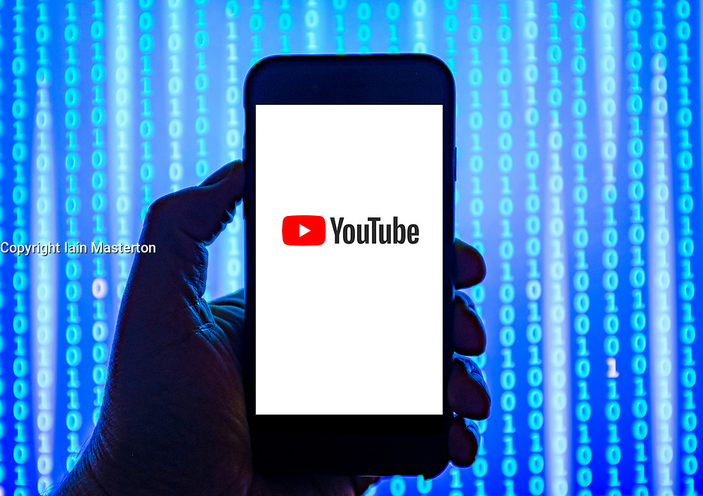 Person holding smart phone with YouTube   logo displayed on the screen. EDITORIAL USE ONLY