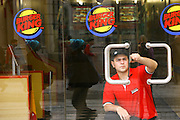 Turkey, Istanbul, A worker of Burger King is cleaning the glass doors in the very popular and western Istiklal street in Istanbul.