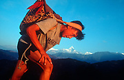 A young Nepali boy is undergoes a recruitment test for the Gurkha Regiment called the Doko race, part of a tough endurance series to find physically perfect specimens for British army infantry training, on 16th January 1997, in Pokhara, Nepal. Carrying 30kg of river stones in a traditional Himalayan doko (basket) for 3km up foothills within 37 minutes to pass.  60,000 boys aged between 17-22 (or 25 for those educated enough to become clerks or communications specialists) report to designated recruiting stations in the hills each November, most living from altitudes ranging from 4,000-12,000 feet. After initial selection, 7,000 are accepted for further tests from which 700 are sent down here to Pokhara in the shadow of the Himalayas. Only 160 of the best boys succeed in the journey to the UK. Nepal has been supplying youths for the British army since the Indian Mutiny of 1857. (Photo by Richard Baker / In Pictures via Getty Images)
