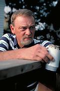 Man age 54 relaxing on deck enjoying evening cup of coffee.  St Paul  Minnesota USA