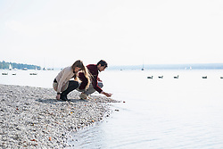 Young couple lake shore gathering pebbles
