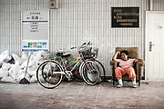"A Chinese woman takes a rest close to her working tools in Tiananmen Square's underground pedestrian passage in Beijing, China, July 19, 2014. <br /> <br /> This image is part of the series ""24/7"", an ironic view on restless and fast-growing Chinese economy described through street vendors and workers sleeping during their commercial daily activity. <br /> <br /> © Giorgio Perottino"