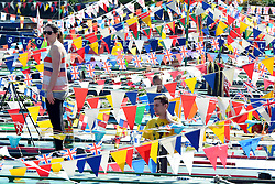 © Licensed to London News Pictures. 06/05/2013. London, UK A man and a woman are camouflaged against a sea of flags flying from the boats. A Colourful gathering of canal boats in the hot bank holiday sunshine today in West London 6th May 2013. Organised by volunteers from Inland Waterways Association (IWA), The Canalway Cavalcade, which has taken place in Little Venice every year since 1983, sees around 130 boats moored along a stretch of the Grand Union Canal in London. Photo credit : Stephen Simpson/LNP
