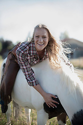 Portrait of a mid adult woman lying on the back of horse in farm and smiling, Bavaria, Germany