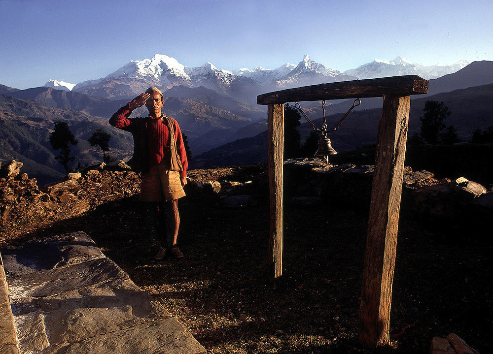 Gurkha L.Cpl Mairaj Thapa near the village prayer bell in his remote mountain village of Shankar Pokhari. The Himalayan mountain range is seen behind.1969. Photographed by Terry Fincher