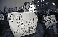 """November 15, 2016, Chris Saudinger, a writer from New Orleans, holds a protest sign """"can't drain this swamp"""" during a protest that over 150 people participated in against the Dakota Access Pipeline in New Orleans outside the US Army Corp of Engineers headquarters in a show of solidarity with the Standing Rock Sioux tribe, whose fight against the pipeline has made international news."""