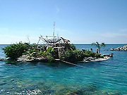 """Eco-pioneer Richard """"Rishi"""" Sowa designed and built an artificial island kept afloat by 100,000 plastic bottles.<br /> <br /> Spiral Island II is actually Rishi Sowa's second artificial island. He built the first one in 1998, near Puerto Aventuras, using 250,000 plastic bottles to keep it afloat. Sadly, his recycled island was destroyed in 2005, when Hurricane Emily passed through the area. Most of Spiral Island was washed up on the beach, but Sowa decided to build a whole new island, in a safer area.<br /> <br /> And that's how Spiral Island II came to be. With the help of volunteers, Rishi Sowa gathered around 100,000 plastic bottles and hand-built his second recycled island, in a lagoon that offers protection from bad weather. The new island features a house, beaches, 2 ponds and a solar-powered waterfall, but its creator says Spiral Island II is and always will be an eco-work-in-progress. Although smaller than its predecessor (only 20 meters in diameter), you can expect the new Spiral Island to increase in size, significantly.<br /> <br /> One of the most impressive DIY projects ever attempted, Spiral Island has inspired volunteers to come to Mexico and help Rishi Sowa improve his creation. But while some believe it a perfect environmental design, built entirely of recycled materials, there is some controversy surrounding Spiral Island. There are those who believe that if the island gets destroyed by a hurricane, again, the materials used to build it (mainly plastic bottles, sand, mangrove plants) will litter the waters of the Atlantic.<br /> ©Spiral Island /Exclusivepix"""