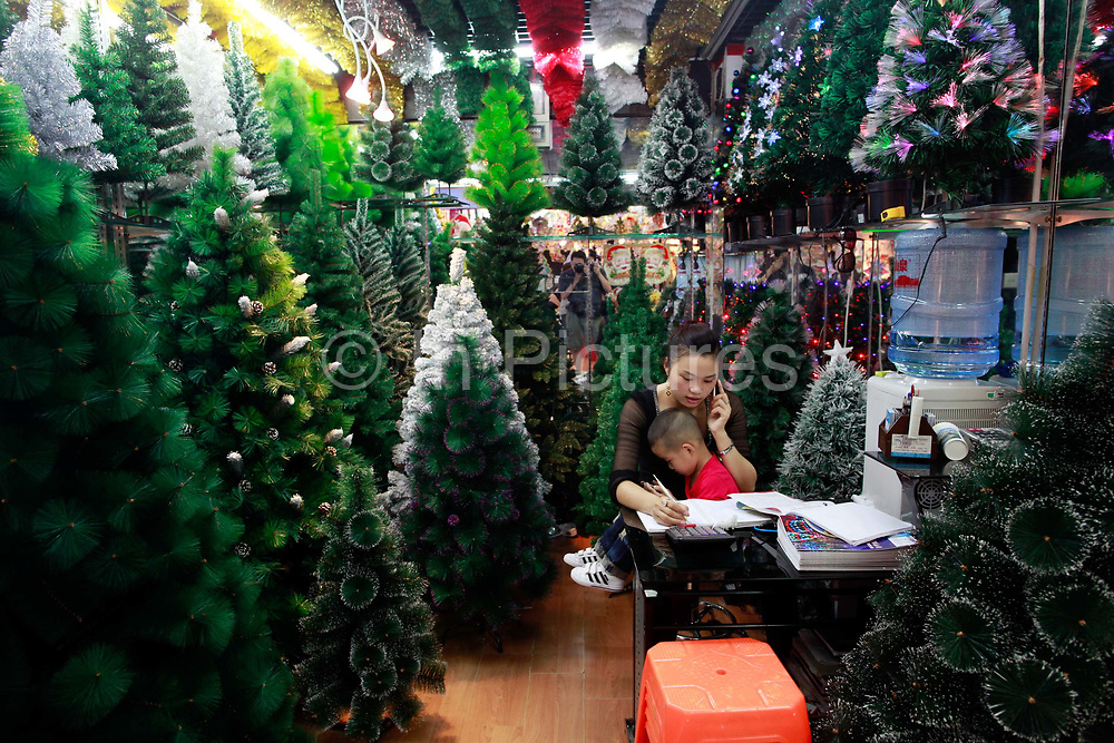 A woman holding her son sits in her stall selling plastic Christmas trees at the Yiwu International Trade City in Yiwu, Zhejiang Province, China on Sunday, 11 September 2011.   As the trading hub for small and medium manufacturers and exporters in the Yangtze River Delta region, Yiwu faces an uncertain future as export orders decline due to the slow economic recoveries of China's two largest trading partners, Europe and the United States