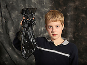 A boy holds a gun in a bag.  This image is part of a series showing the identical scene in far infrared light.  The comparison of image in the series show the power of far infrared light to see through materials like the plastic bag teh boy is holding.