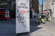 Graffiti now covers a year-old social distance sign at the corner of Oxford Street and Totenham Court Road, during the third lockdown of the Coronavirus pandemic, on 29th March 2021, in London, England.