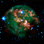 A dying star (center) surrounded by a cloud of glowing gas and dust. The star and its cloud halo constitute a 'planetary nebula' called NGC 246. Spitzer Space Telescope.